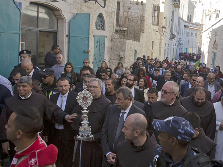 Clergymen carry a wooden relic believed to be from Jesus' manger outside the Church of the Nativity, traditionally believed by Christians to be the birthplace of Jesus Christ, in the West Bank city of Bethlehem, on Saturday.