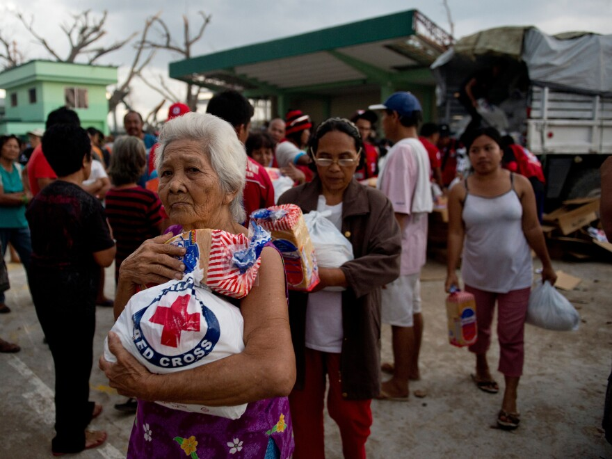 An elderly woman and others leave after getting some help from Red Cross volunteers Monday in Dagami, the Philippines, about 20 miles south of the city of Tacloban. Millions of people need assistance because their homes were destroyed by Typhoon Haiyan on Nov. 8.
