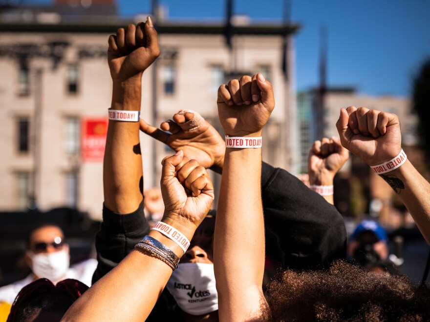 "Black Lives Matter protesters display wristbands reading ""I VOTED"". Activists warn Black and Latino voters are being flooded with disinformation intended to suppress turnout in the election's final days."