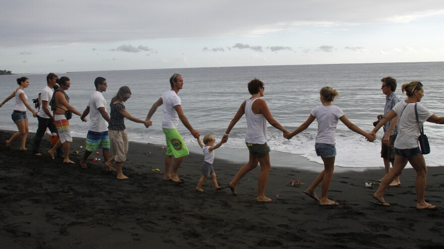 Mourners form a human chain along a beach on the French island of Reunion after Talon Bishop, 22, was killed by a shark in February.