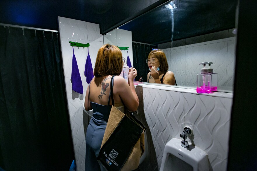 M. gets ready at the bar where she works in a red-light district in Pattaya.