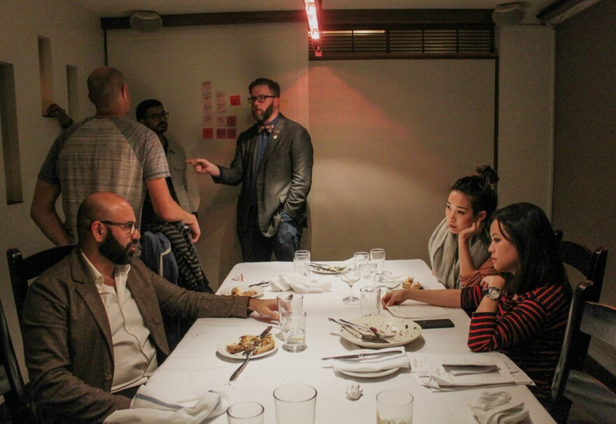 Make America Dinner Again guest Affan Khokhar (left, seated) talks with hosts Tria Chang and Justine Lee (front right, seated) after the dinner as guests (from left to right) Afam Agbodike, Walter Rodriguez and Nick Tucker continue their conversation.