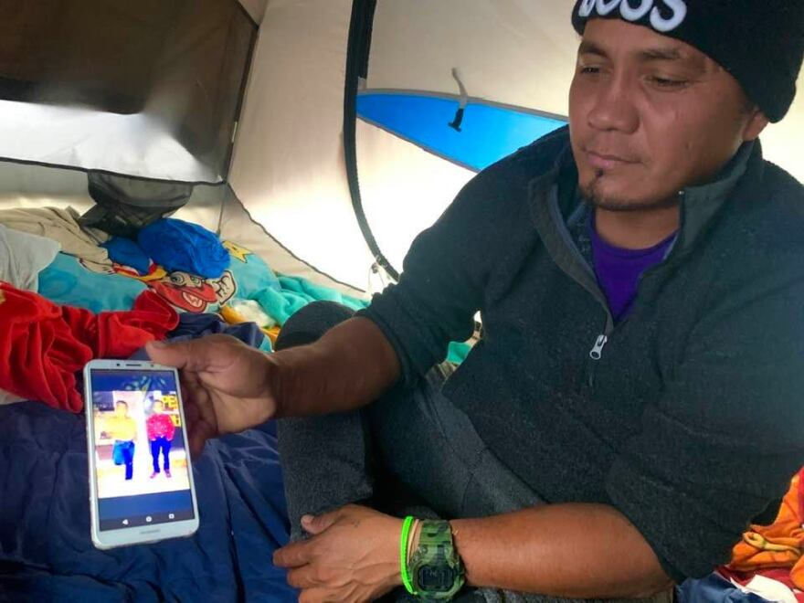 Roberto Gonzalez shows a photo of his two boys inside the tent he's been living in in Matamoros, Mexico.