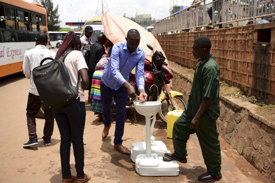 A public hand-washing station for passengers boarding a bus was set up as a cautionary measure against the coronavirus at Nyabugogo Bus Park in Kigali, Rwanda. The photo was taken on March 11.