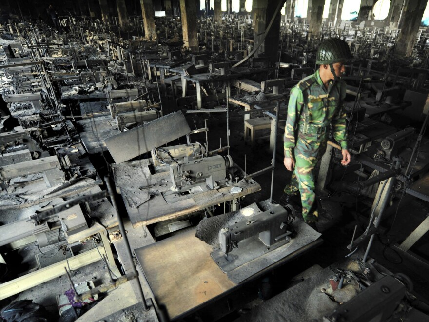A Bangladeshi police officer walks between rows of burned sewing machines in the Tazreen Fashions garment factory outside Dhaka, Bangladesh, in Nov. 2012.
