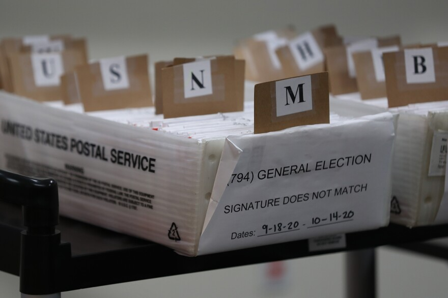 Mail-in ballots that need to be reviewed because of signature discrepancies sit in boxes at the Miami-Dade County Elections Department in Doral, Fla., on Oct. 15. Signature problems are a frequent reason that ballots are rejected, though many states allow voters to fix those problems before Election Day.