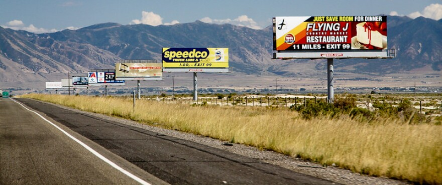 A photo of a road in Utah with many billboards on the side.