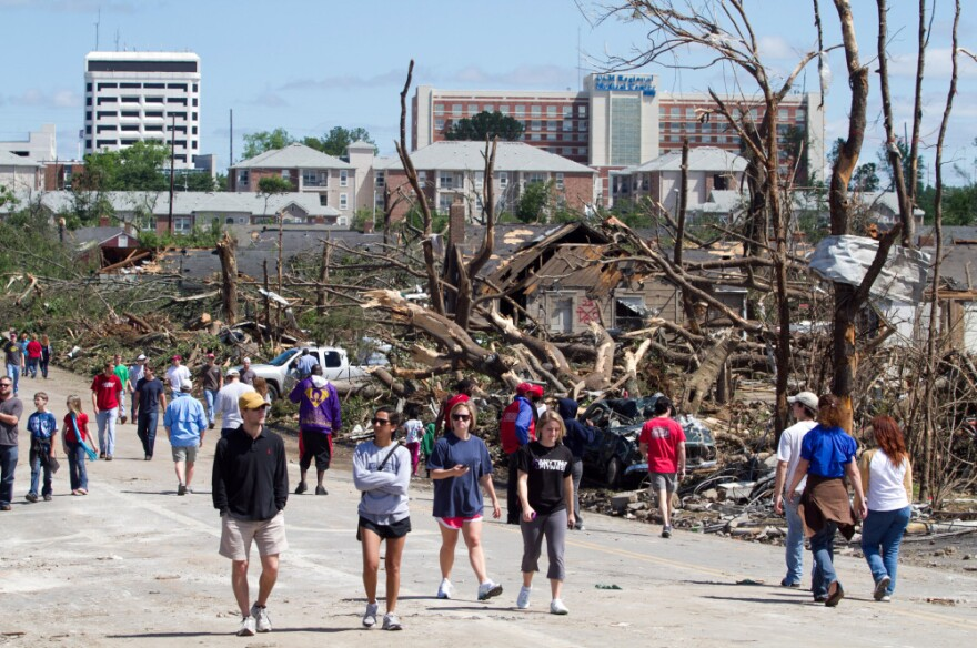 In the aftermath of a severe tornado, residents wander the steets near downtown Tuscaloosa surveying the damage.