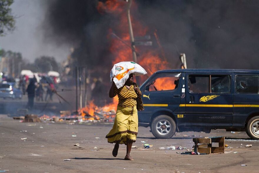 A woman carrying groceries on her head runs away as Zimbabwe's opposition supporters set up a burning barricade.