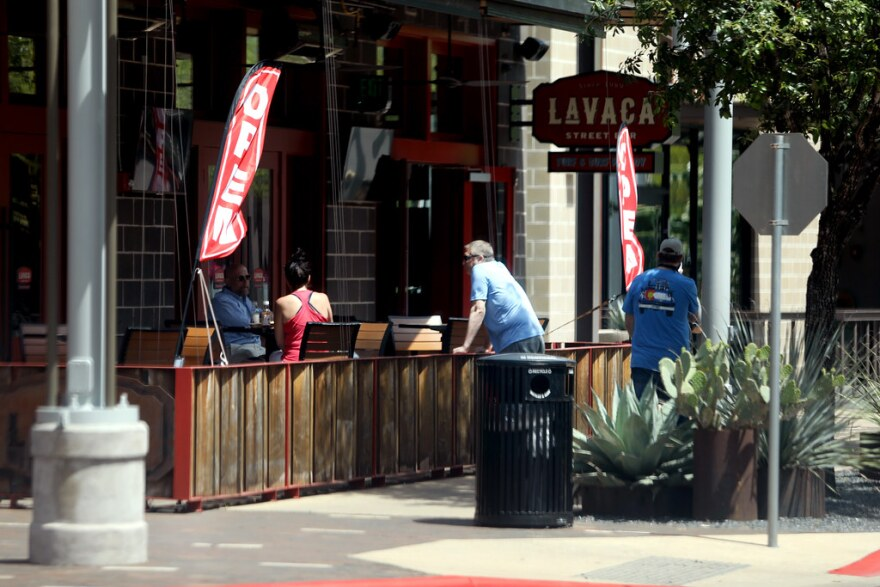 Patrons sit outside the Lavaca Street Bar in the Domain on May 1, as the Texas economy is slowly opens.