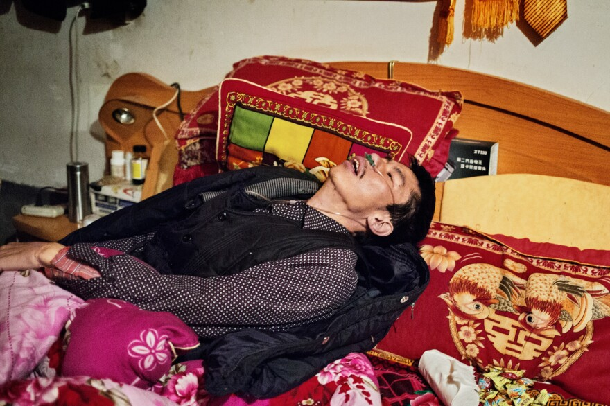 He Quangui, moments after he tried to suffocate himself while the rest of the household was asleep. His wife pulled toilet paper out of his nose, a plastic bag out of his mouth and untied his hands which he bound tightly with white cloth. He Quangui had pulled his oxygen tube off and muttered a prayer to the Chinese gods to take him quickly to the other world.