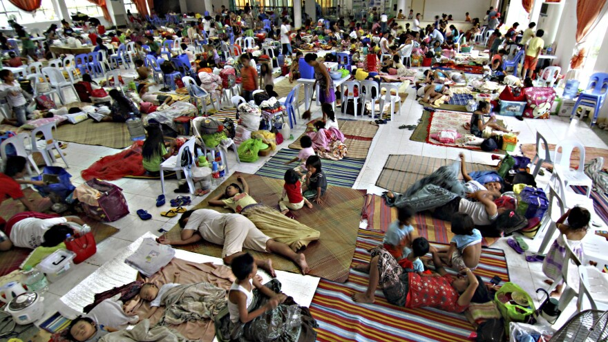 Hundreds of residents take shelter Friday inside the provincial capitol of Surigao city close to central Philippines in anticipation of typhoon Hagupit which is expected to hit land Saturday afternoon. About a year ago the country was lashed by Typhoon Haiyan, which left more than 7,300 people dead.