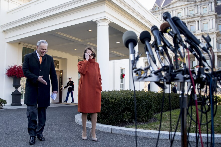 Democratic House leader Nancy Pelosi and Senate Minority Leader Chuck Schumer approach microphones outside the White House after a contentious meeting with President Trump.