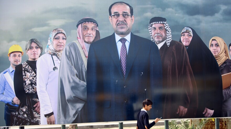 A man walks past a huge election poster in Baghdad promoting Iraqi Prime Minister Nouri al-Maliki (center) and his political allies. Maliki has ruled for eight years and is seeking another four years.