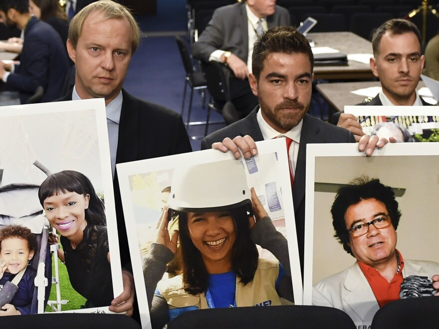 Family members hold photos of victims killed on Ethiopian Airlines Flight 302 and Lion Air Flight 610 on Tuesday.