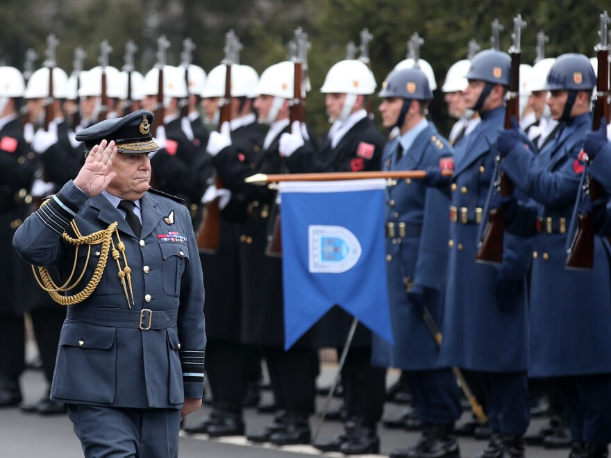 British Air Chief Marshal Sir Stuart Peach salutes an honor guard during during an official welcoming ceremony in Ankara, Turkey in February.