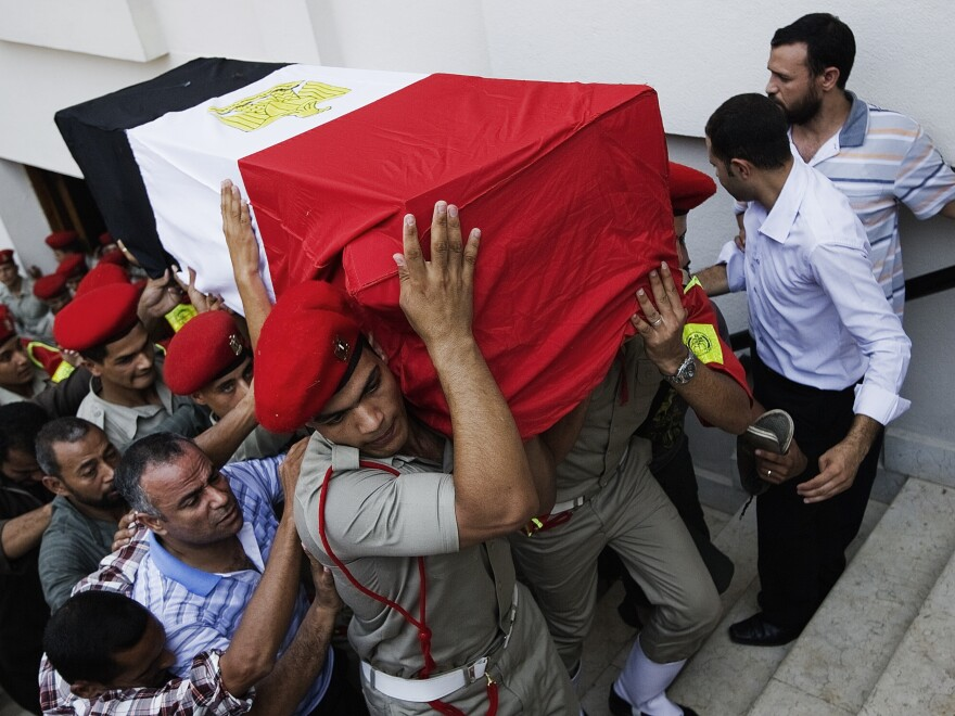 In Cairo on Tuesday, Egyptian Army military policemen carried the coffin of one of the 16 border guards killed during an attack on a crossing post in the northern Sinai on Sunday.