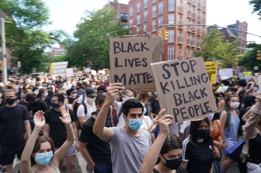 At a rally on Saturday, protesters march and carry signs in New York's West Village as they demonstrate in outrage over the death of George Floyd.