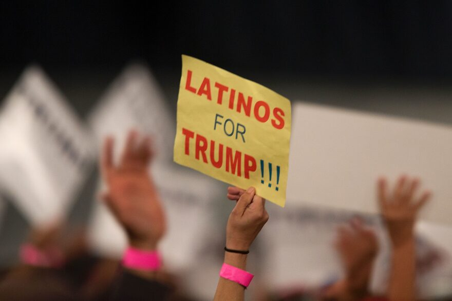 A woman holds a sign expressing Latino support for Republican presidential candidate Donald Trump at his campaign rally at the Orange County Fair and Event Center, April 28, 2016, in Costa Mesa, California. (David McNew/AFP via Getty Images)