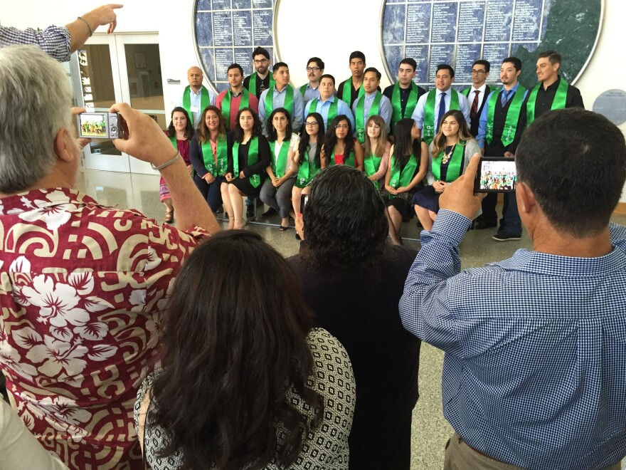The first cohort of the CSin3 program gathers for a group photo as their family members snap pictures.