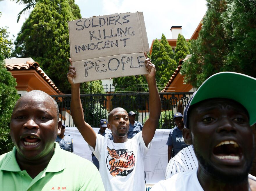 A protester holds a placard during a demonstration of Zimbabwean citizens outside the Zimbabwean Embassy in Pretoria following the announcement of a petrol price hike in Zimbabwe and the recent shut down of mobile phone networks and internet services.