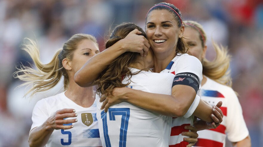 U.S. forward Alex Morgan celebrates her hat trick with defender Tobin Heath (17) and other teammates during the second half of a Tournament of Nations soccer match against Japan in July 2018.