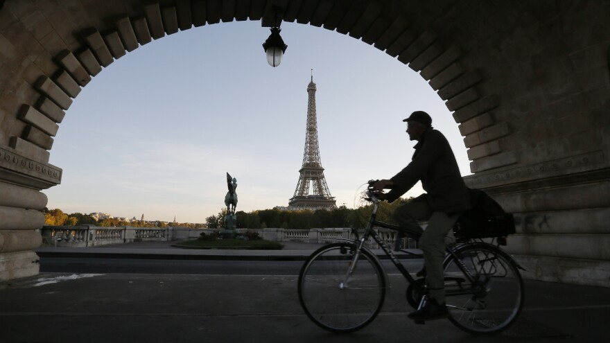 A man takes an early morning bicycle ride across a bridge near the Eiffel Tower in Paris.