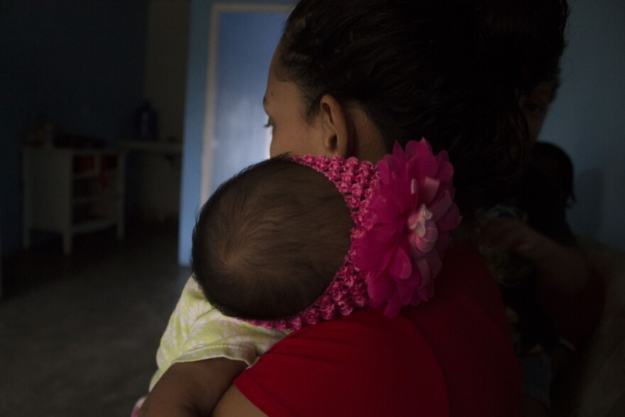 A Honduran mother holds her newborn daughter in their apartment. She delivered her baby in a local hospital in the Rio Grande Valley, but she and her daughter were expelled to Mexico, along with the rest of her family.