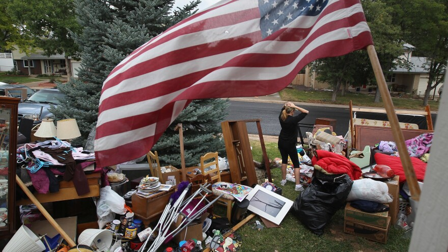 Julie Holzhauer stands among her family's possessions after being evicted from her home in Centennial, Colo., in 2011.