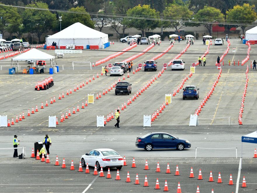 People wait for COVID-19 vaccinations in their vehicles at the Fairplex fairgrounds in Pomona, Calif., last month. The White House announced on Friday that active duty military personnel will soon be deployed to assist at vaccination sites, starting this month in California.