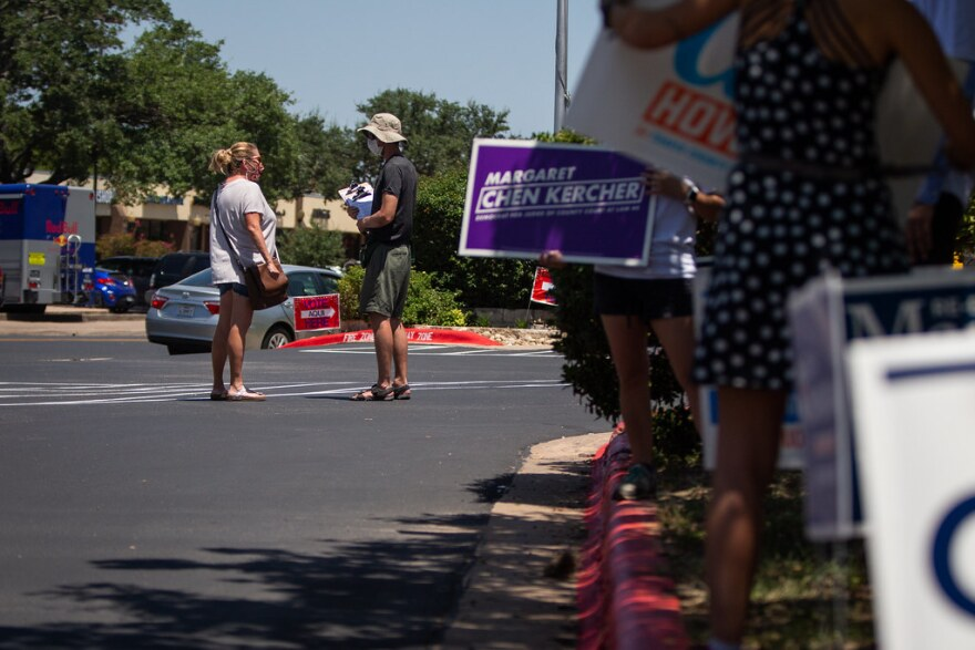An electioneer talks to a voter outside Ben Hur Shrine during the primary election runoff in July.