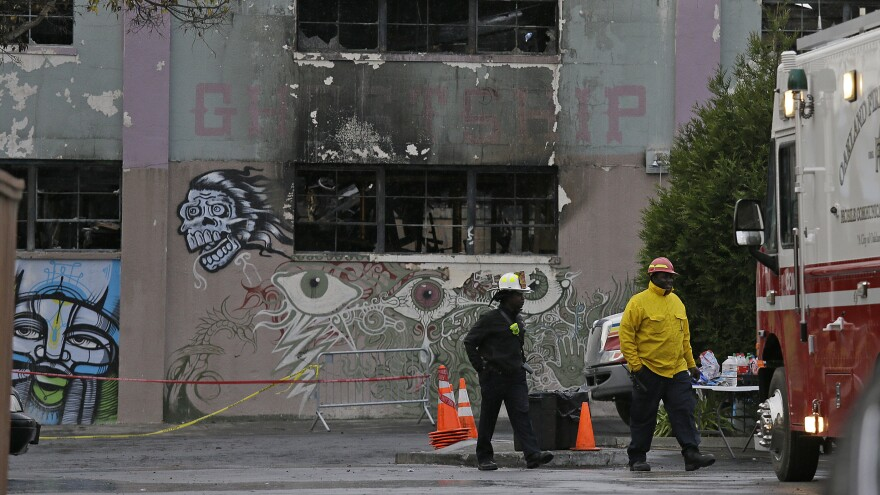 Fire officials walk past the Ghost Ship warehouse following the deadly 2016 fire in Oakland.