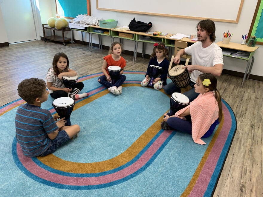 Kids sit in a drum circle with teacher