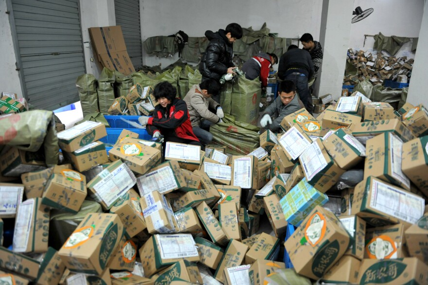 Workers sort through boxes of goods Friday at a delivery company in Lin'an in east China's Zhejiang province. Singles Day on Nov. 11 is promoted by e-commerce giant Alibaba as the world's biggest online shopping event.