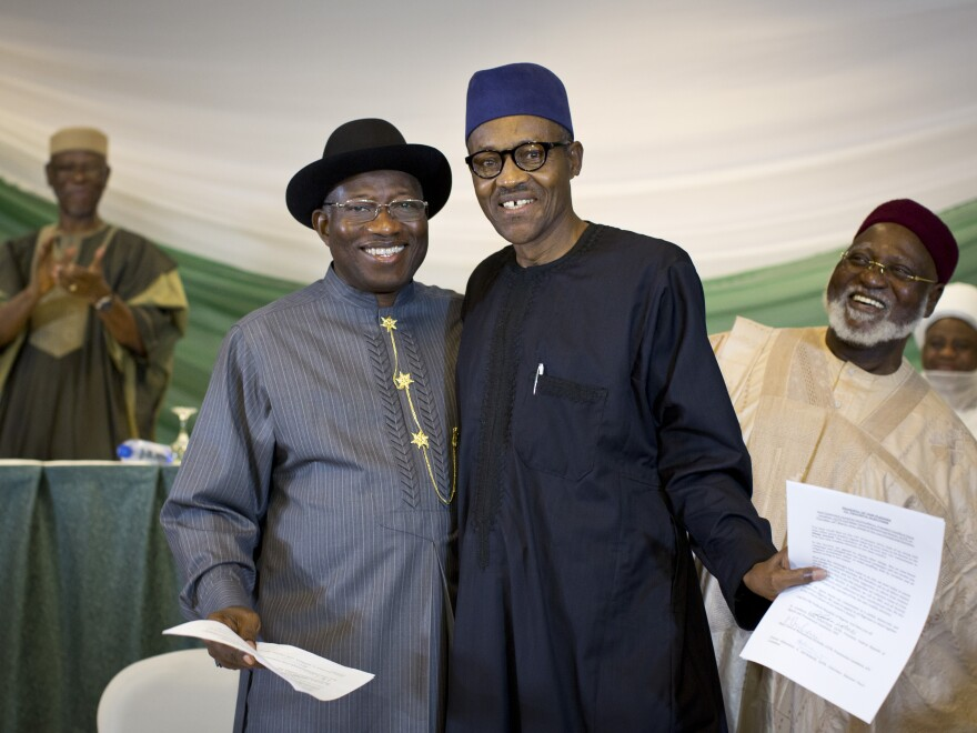 "Nigeria's President Goodluck Jonathan, center left, and opposition candidate Gen. Muhammadu Buhari, center right, appear on Thursday in Abuja, the Nigerian capital, after signing a renewal of their pledge to hold peaceful ""free, fair, and credible"" elections. Fighting broke out after the last time the two men faced off at the polls in 2011."