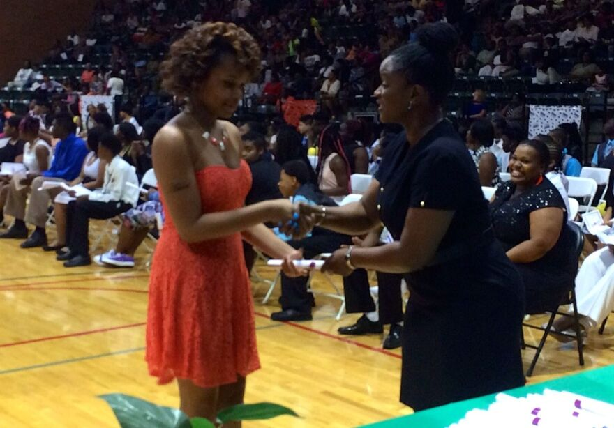Principal GeNita Williams presents certificates to eighth graders at Normandy Middle School
