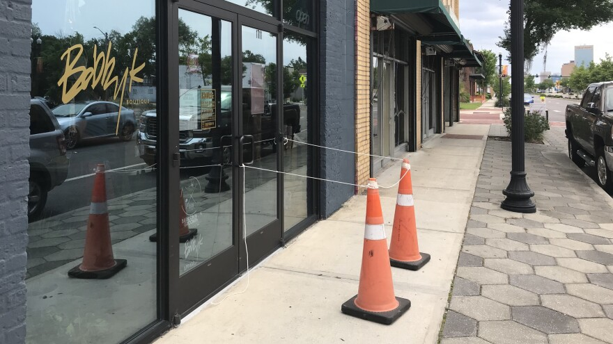 Orange cones mark the space where customers must stop on the sidewalk to pick up internet orders from the BOBBYK Boutique in Springfield. Many businesses in the area are temporarily closed or operating on reduced hours with pick-up only service.