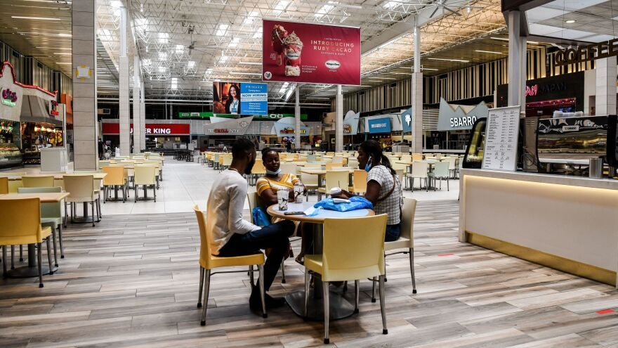 People eat in a deserted food court inside a mall west of Fort Lauderdale, Fla., Monday. U.S. states have been easing restrictions on businesses ahead of Memorial Day, the traditional start of the summer vacation and outdoor season.