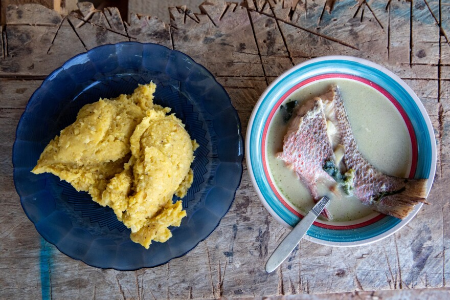 A plate of <em>machuca</em>, boiled and mashed plantains, next to a basil coconut soup with red snapper. Family matriarch Tomasa Guity prepared the food for the family's Sunday meal.