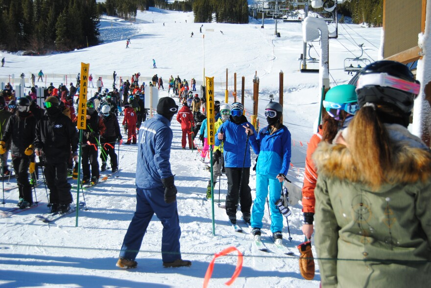 A crowd of skiers stand in line behind yellow 'Wait Here' signs, with ski lifts in the background.