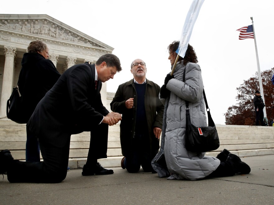 Rev. Brad Wells, left, Rev. Patrick Mahoney and Paula Oas, kneel in prayer in front of the Supreme Court in December as justices hear arguments in the Masterpiece Cakeshop case.