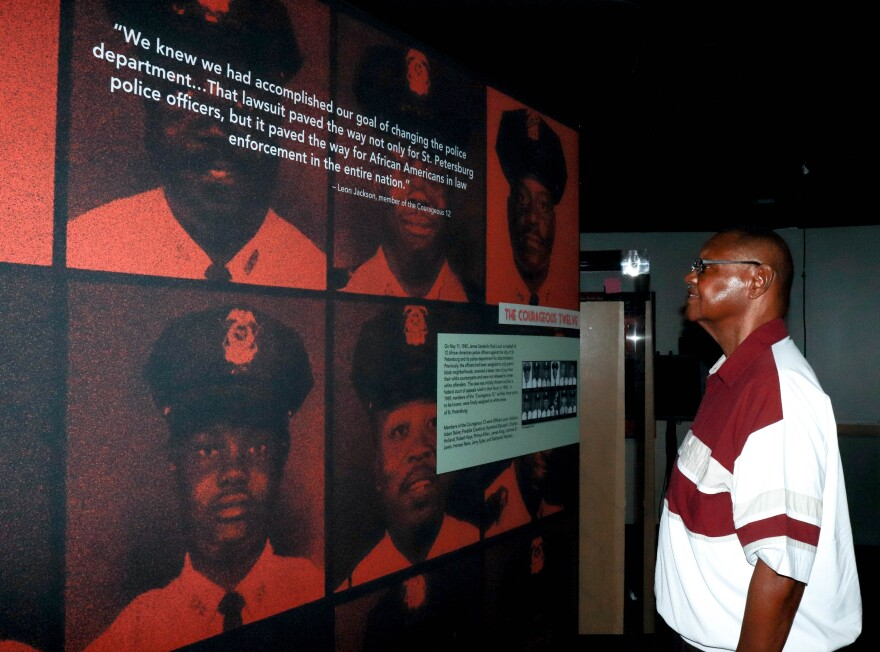 "Leon Jackson looks proudly at the photos of his fellow officers from ""The Courageous 12."""