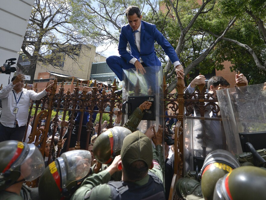 National Assembly President Juan Guaidó, Venezuela's opposition leader, climbs the fence in a failed attempt to enter the compound of the assembly, as he and other opposition lawmakers are blocked from entering.