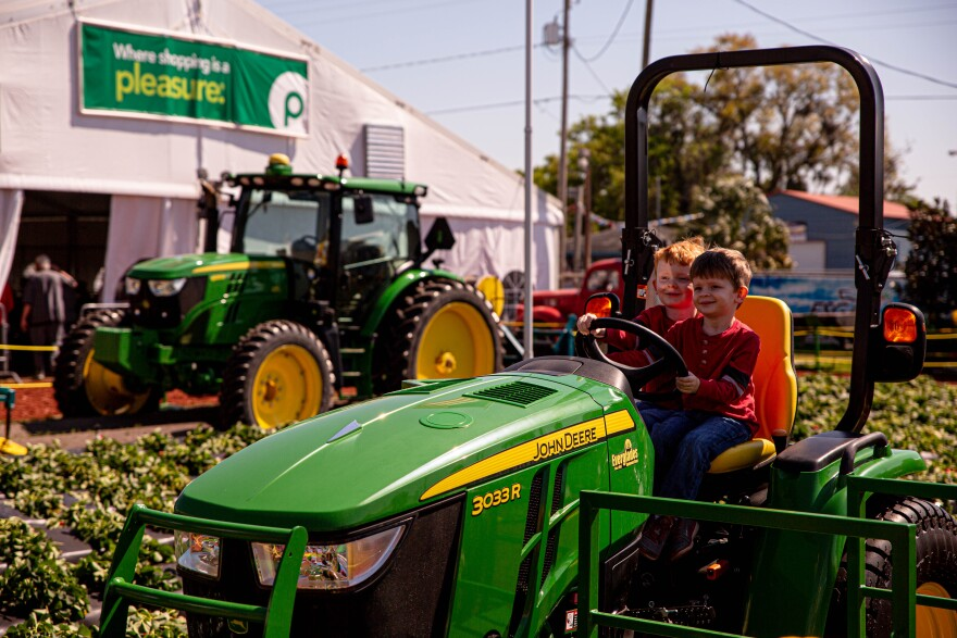 Two children pose for a photo on a tractor with a tractor and a strawberry patch in the background.