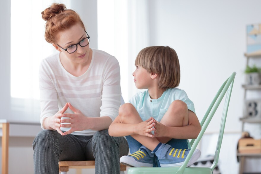 Young, female school psychologist having a serious conversation with a small boy.