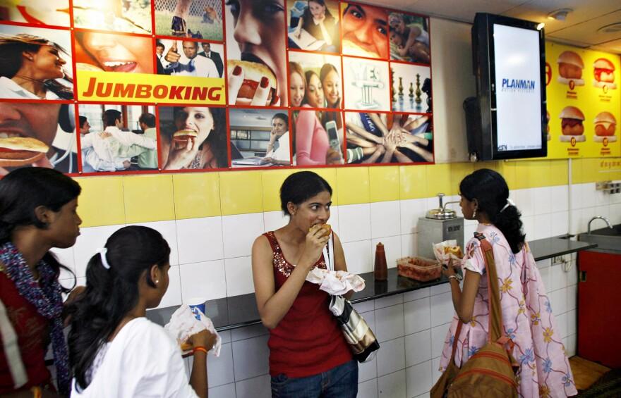 Young Indian women eat the popular food snack<em> vada pav</em> at a Jumboking outlet in Mumbai.
