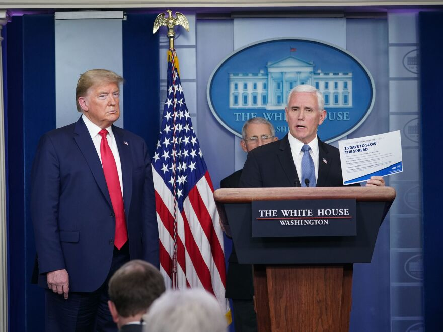 Vice President Pence holds up a copy of the 15-day coronavirus guidelines at a briefing on March 24.
