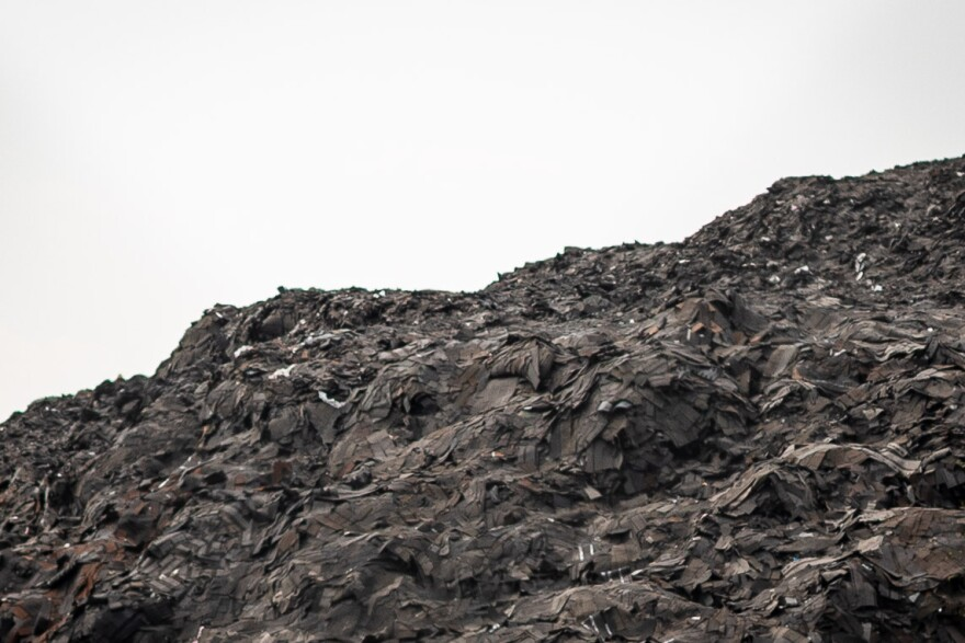 A close up photo of Shingle Mountain's old roofing material pile up on top of eachother.