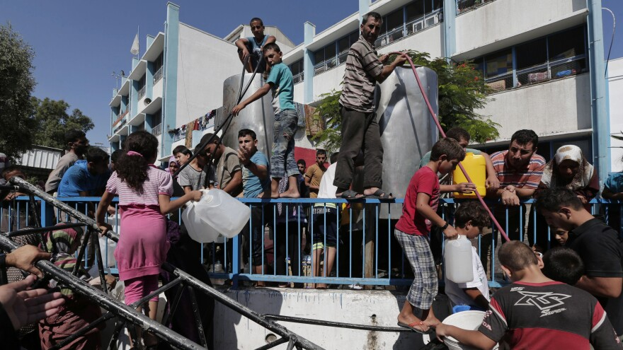 Palestinians displaced by the fighting in Gaza wait to collect water at a U.N. school in Gaza City on Aug. 8.