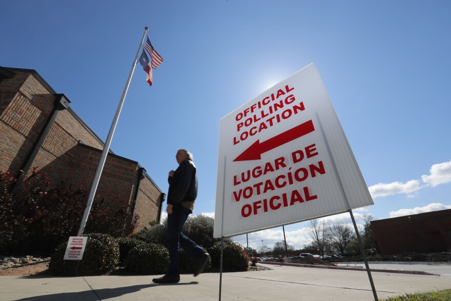 A sign pointing to a polling location in Dallas includes both the English and Spanish language.